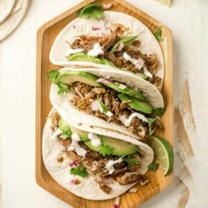 three pork tacos on a wooden tray