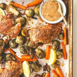 chicken on a sheet pan glazed with mustard with carrots and brussels sprouts