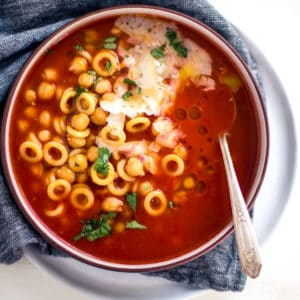 tomato soup with pasta in a bowl with a spoon