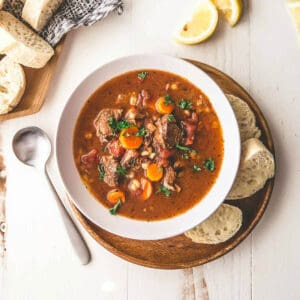 beef and barley soup in a bowl with bread