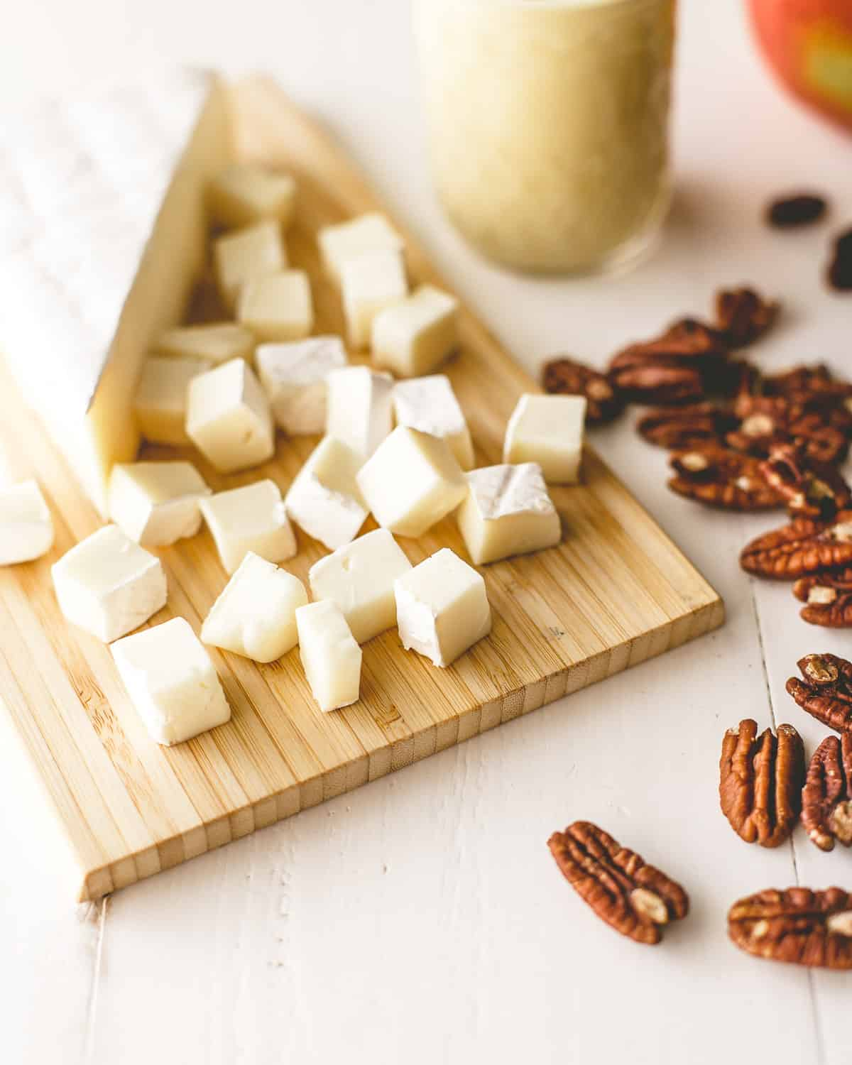 brie and pecans on a white table