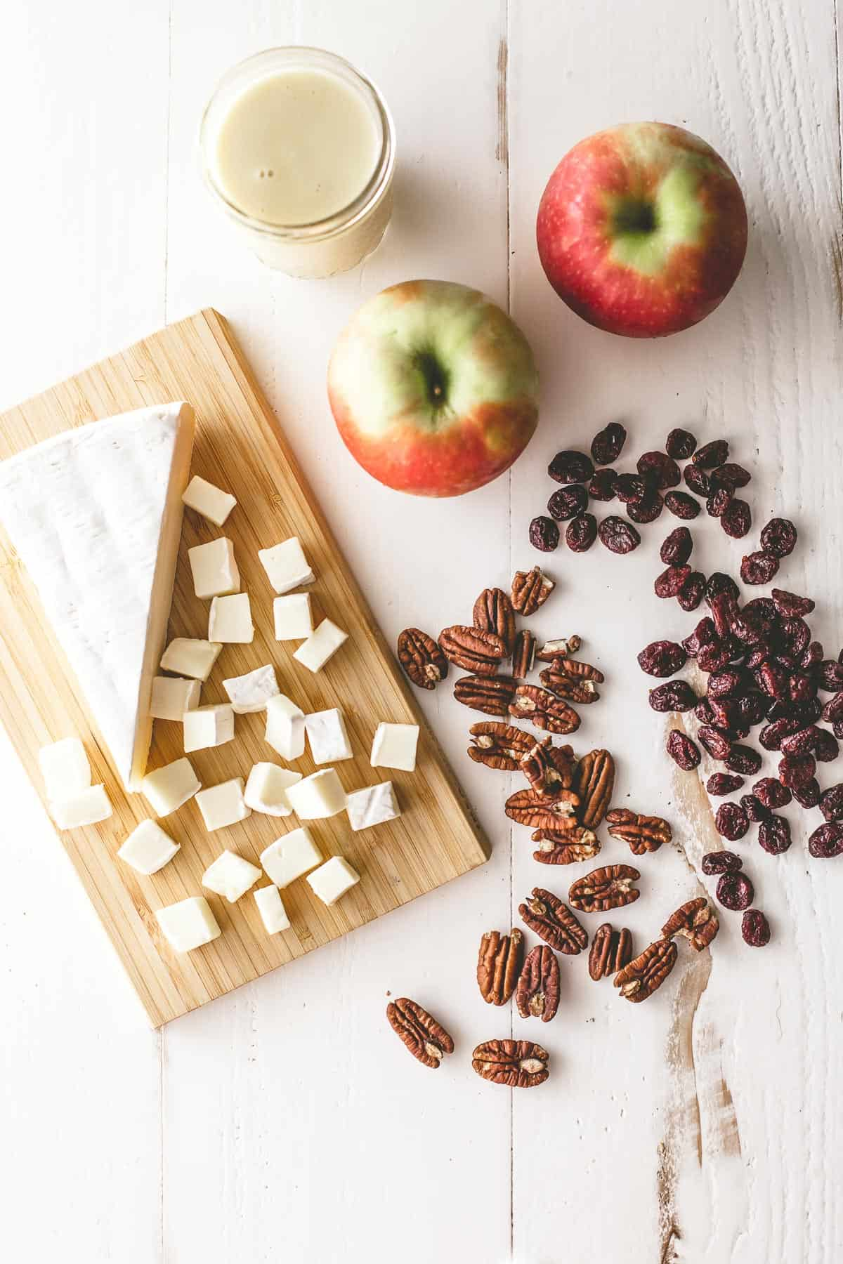 brie, apples and pecans on a white table