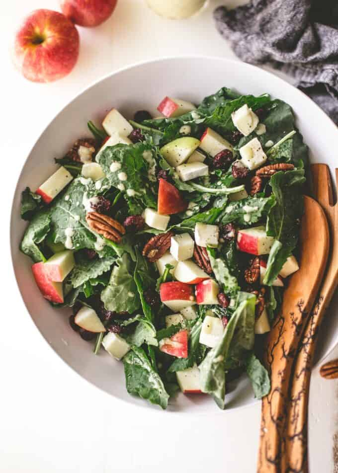 apple salad in a white bowl with salad tongs