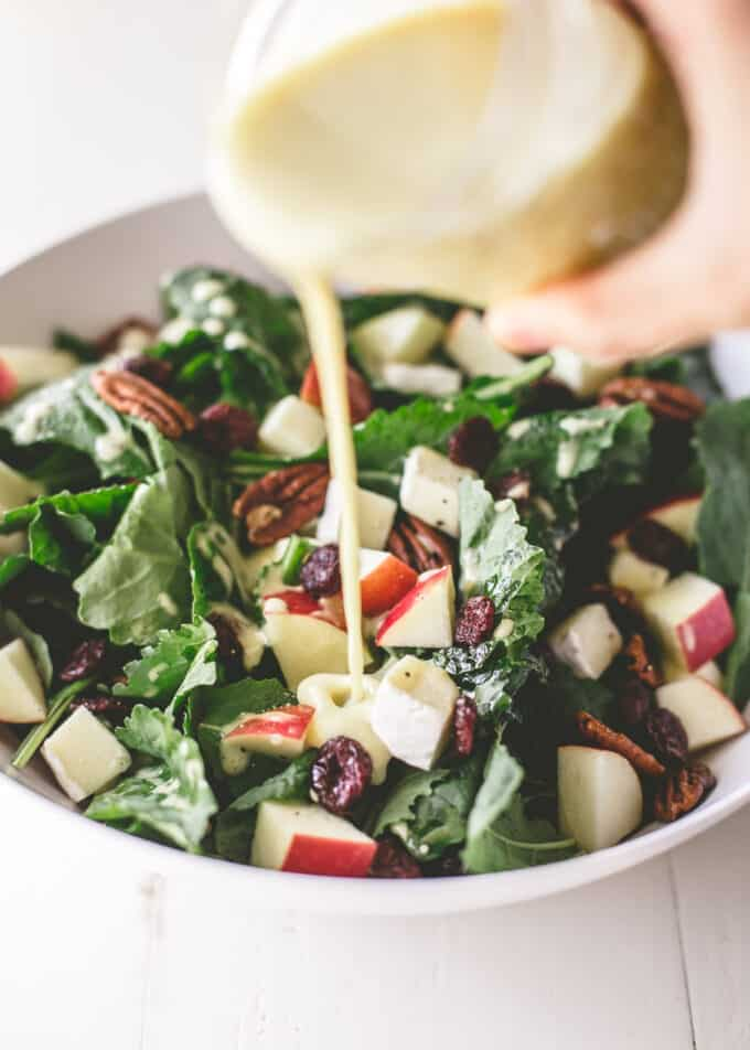 adding vinaigrette to apple salad