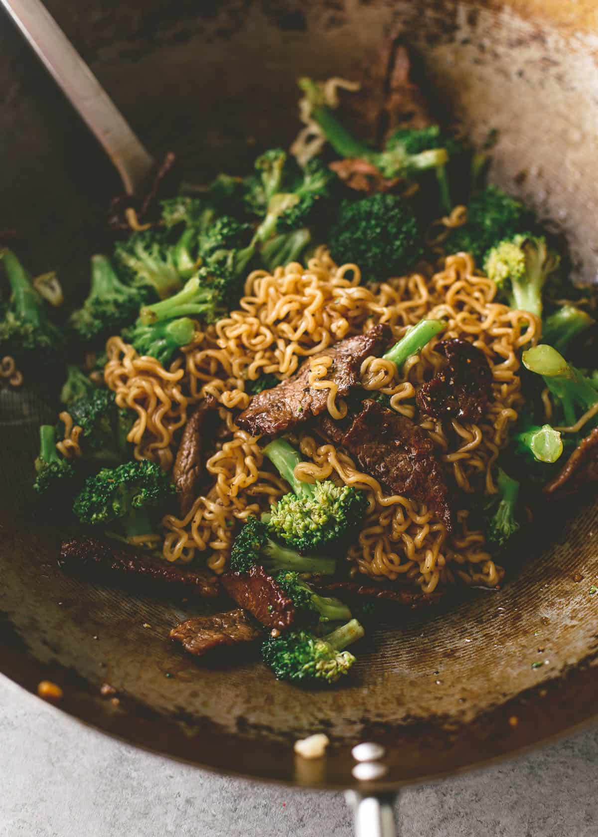 mixing steak and cooked broccoli in a wok
