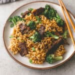 beef and broccoli stir fry on a plate with chopsticks