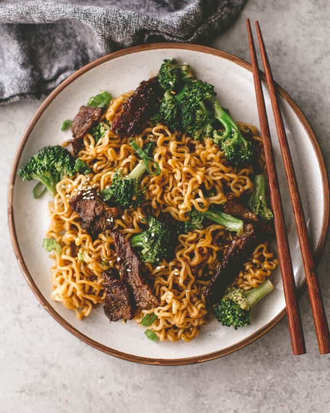 beef and broccoli stir fry on a white plate with chopsticks