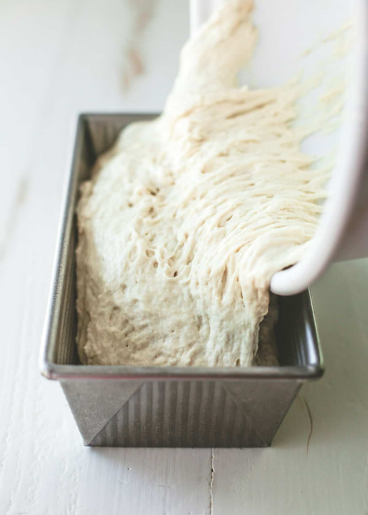 pouring dough into loaf pan