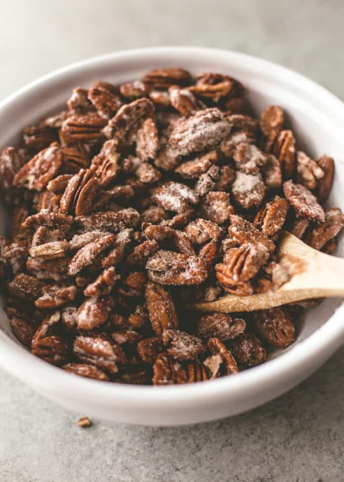 tossing pecans in a bowl with a wooden spoon
