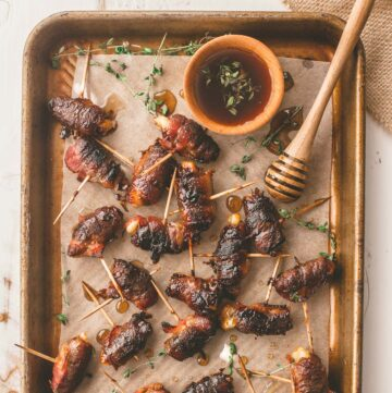 bacon wrapped dates on a parchment lined sheet pan with thyme sprigs