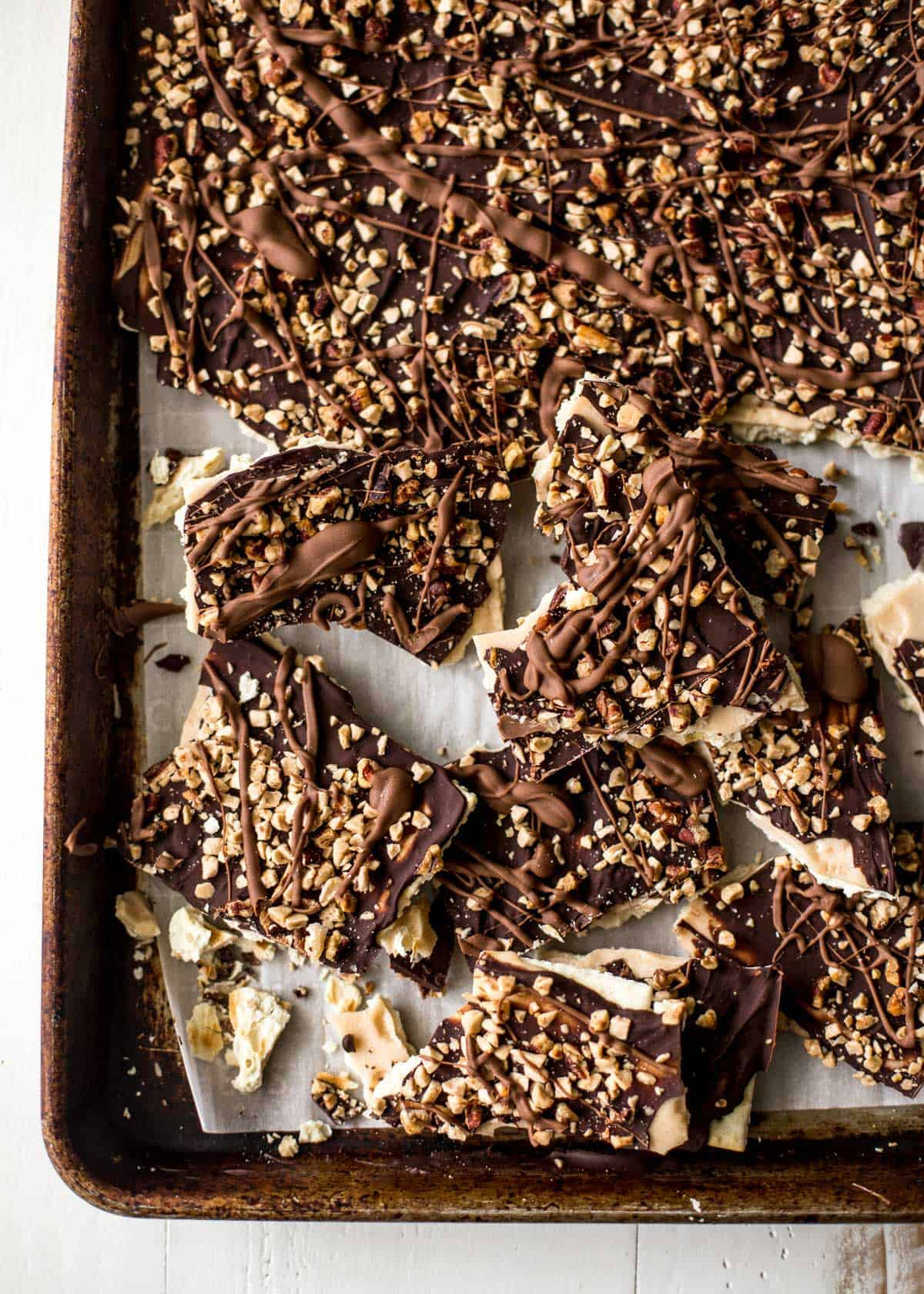 saltine toffee bark pieces on a sheet pan
