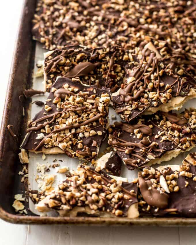 chocolate saltine bark broken into pieces on a sheet pan