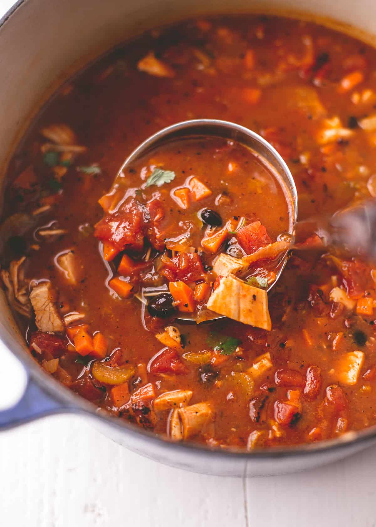 turkey tortilla soup in a dutch oven with a ladle