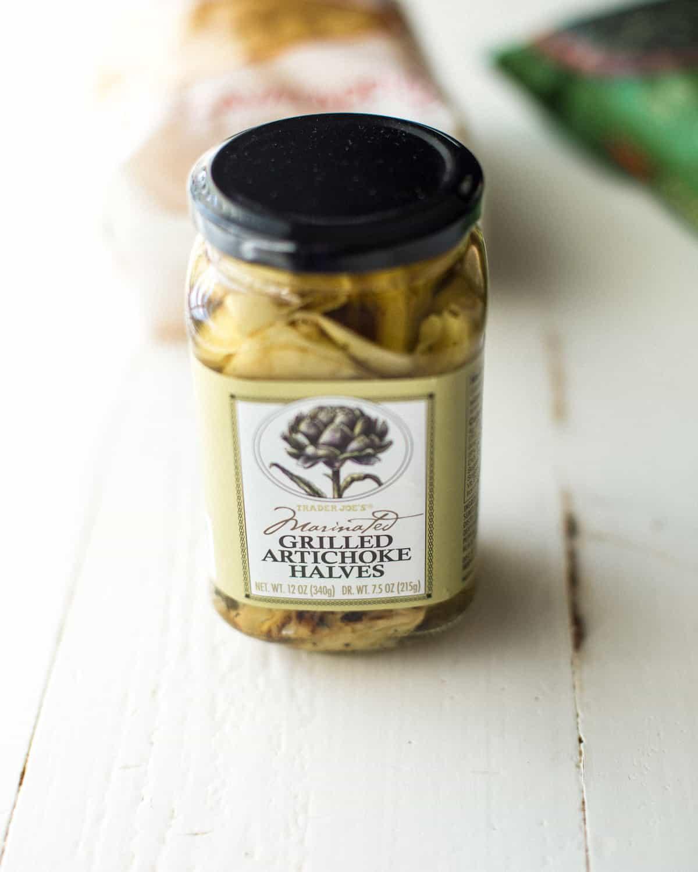 a jar of artichoke hearts on a white table