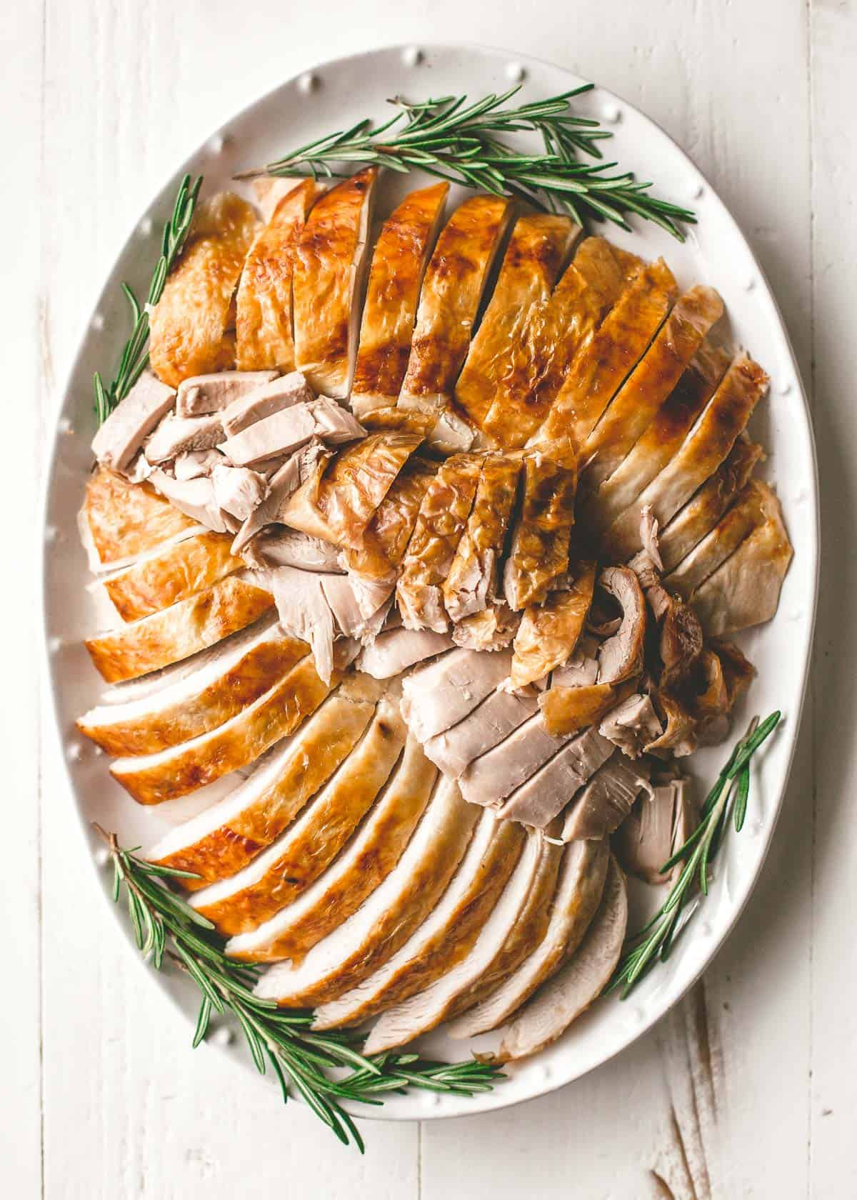 turkey slices on platter with rosemary sprigs