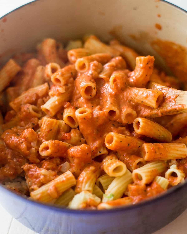 stirring pasta into tomato sauce