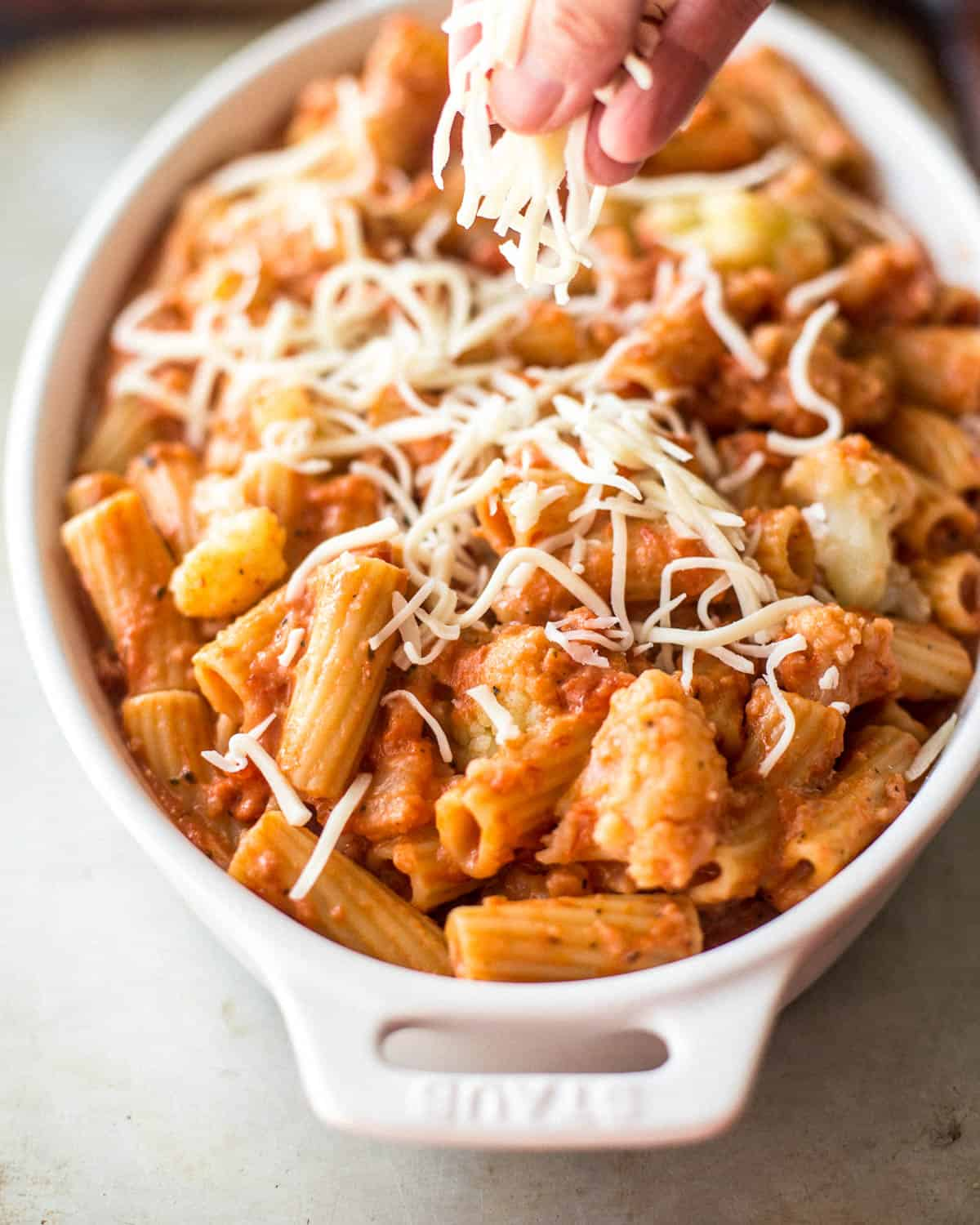 topping casserole with shredded cheese