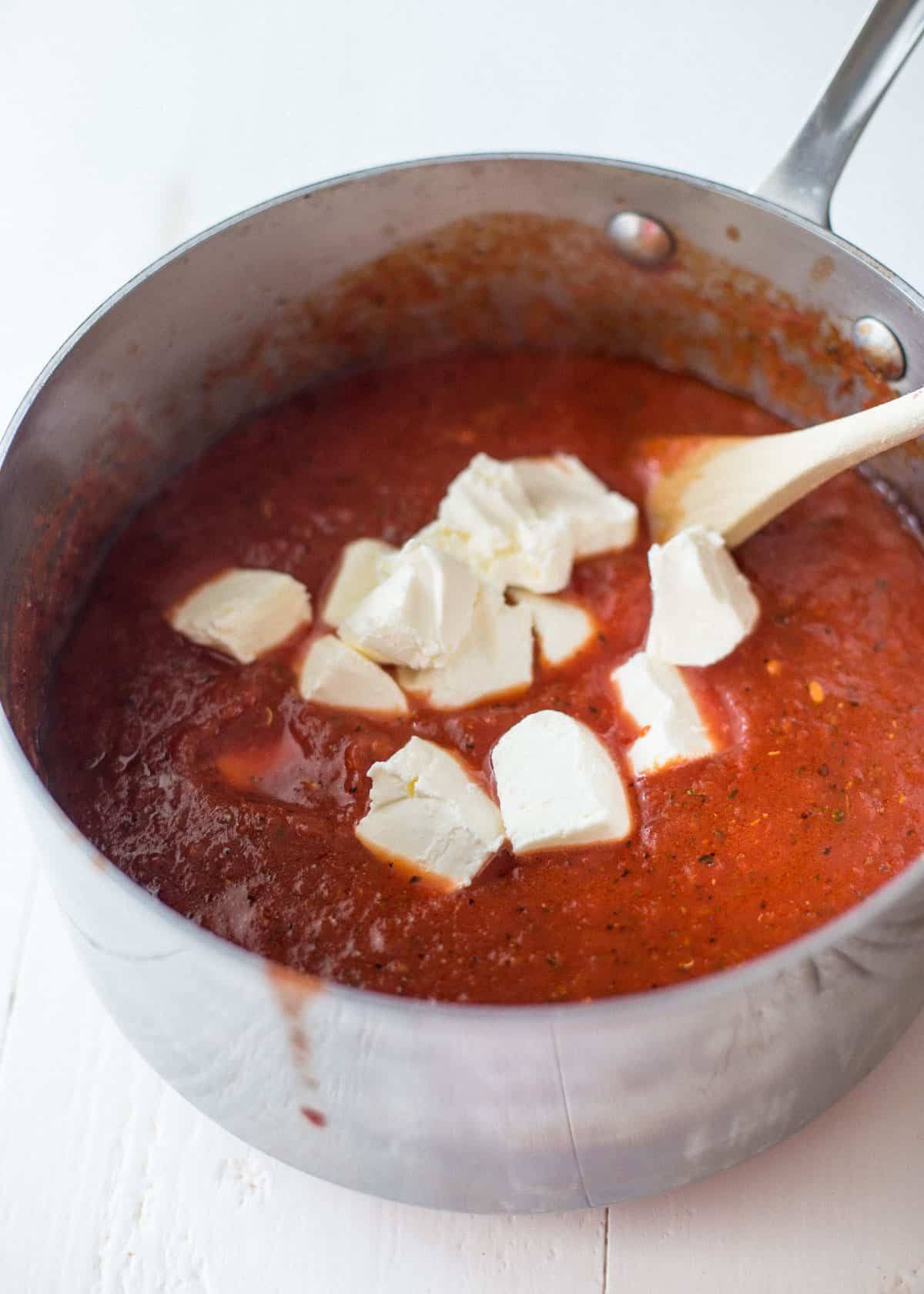 adding cream cheese to tomato sauce