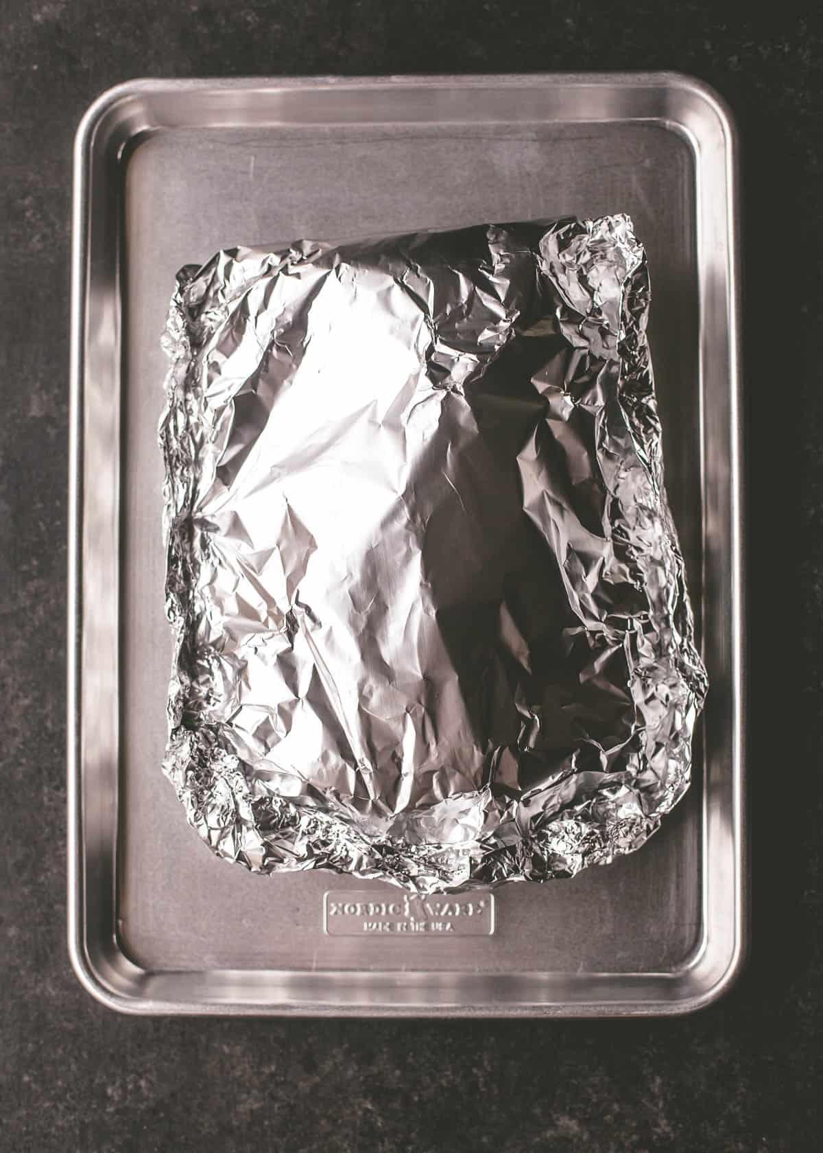 foil wrapped salmon on a sheet pan