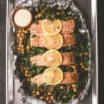 salmon and greens with sauce on a sheet pan