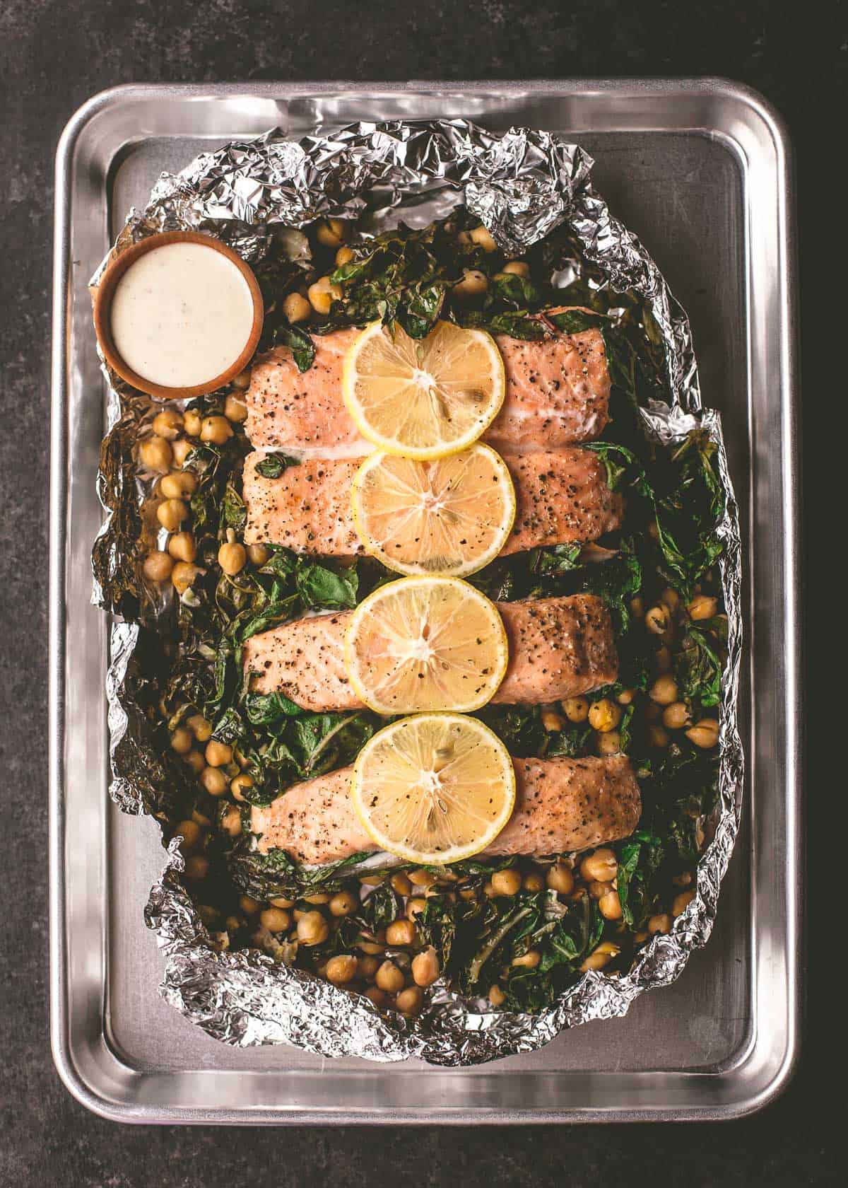 salmon and greens with sauce in foil on a sheet pan
