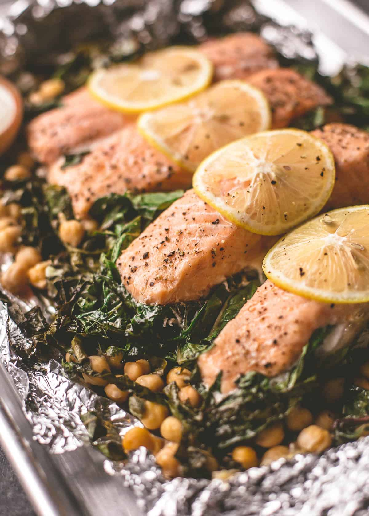 roasted salmon filets on a bed of greens and chickpeas in foil