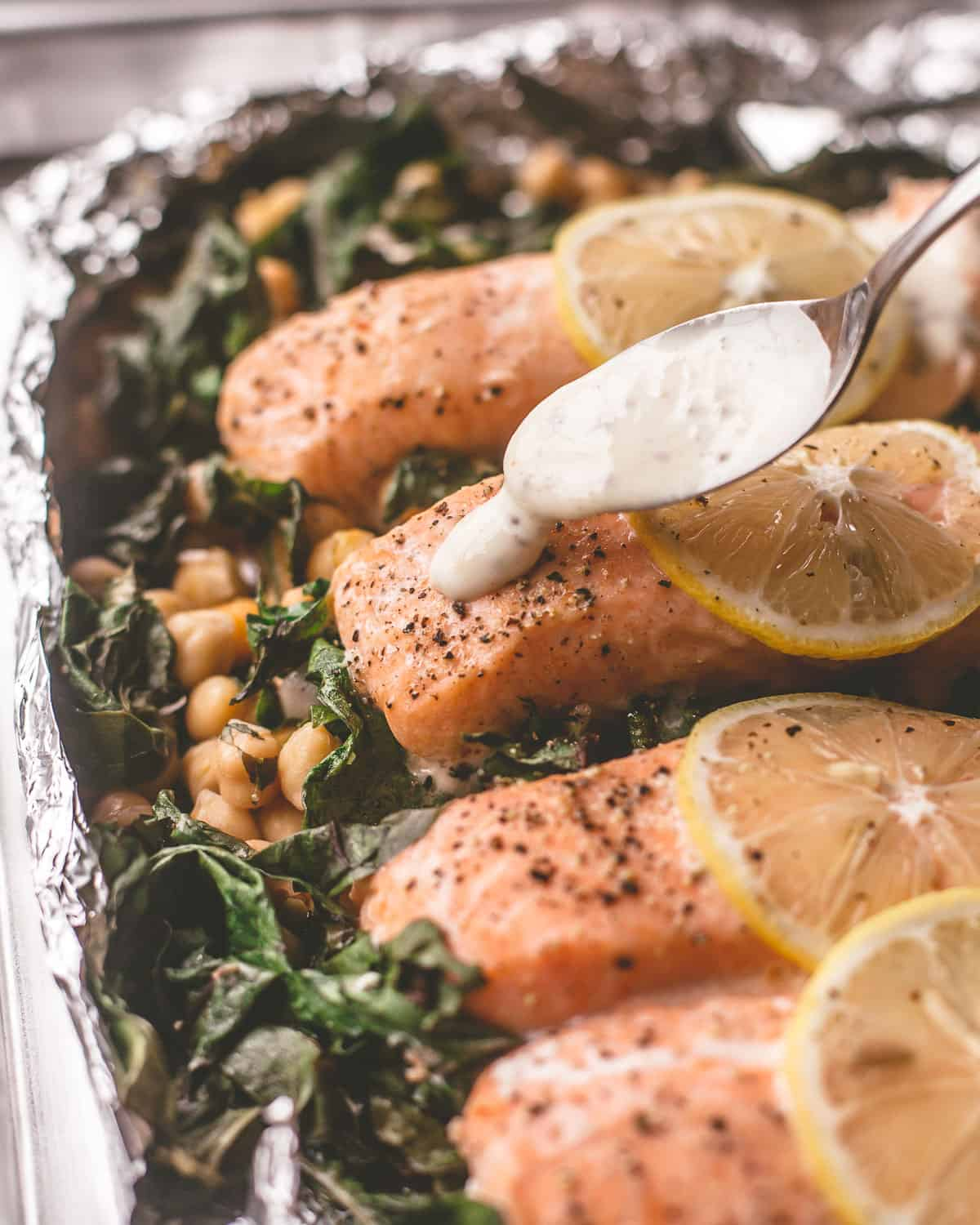 spooning sauce over foil-roasted salmon