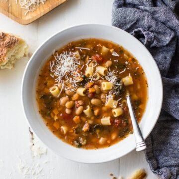 pasta e fagioli in a white bowl with a spoon