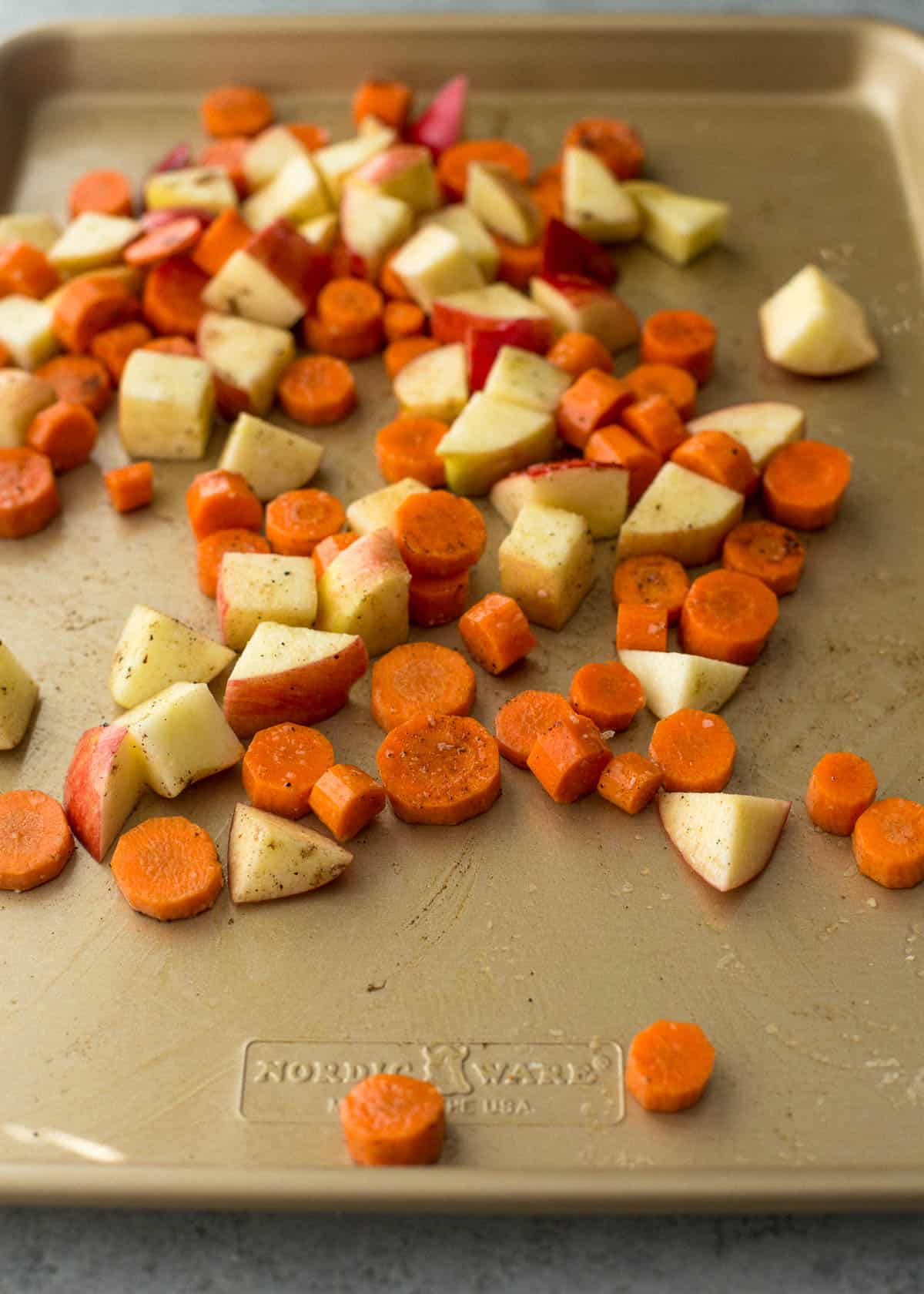 diced carrots and apples on a sheet pan