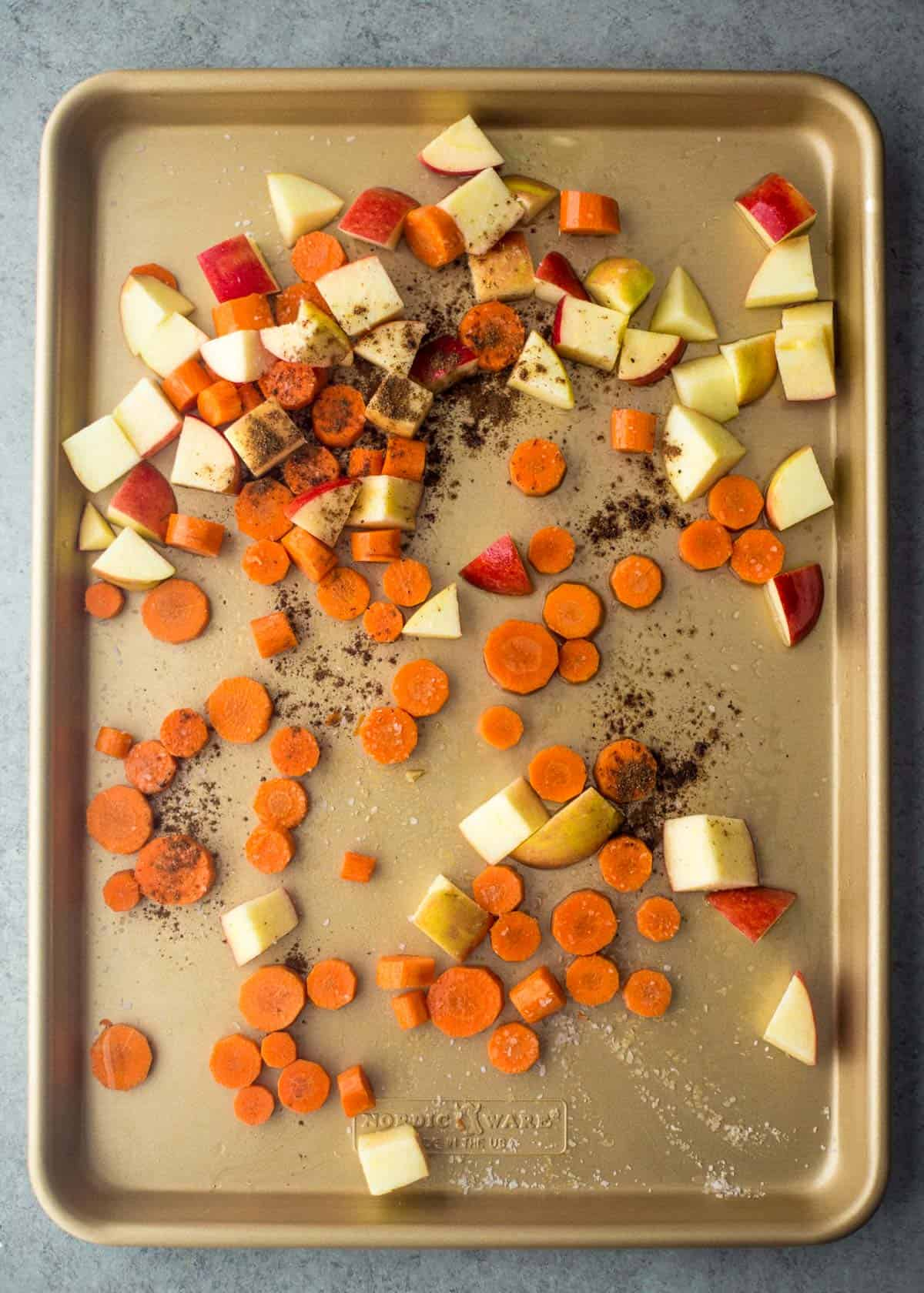 diced raw apples and carrots on a sheet pan