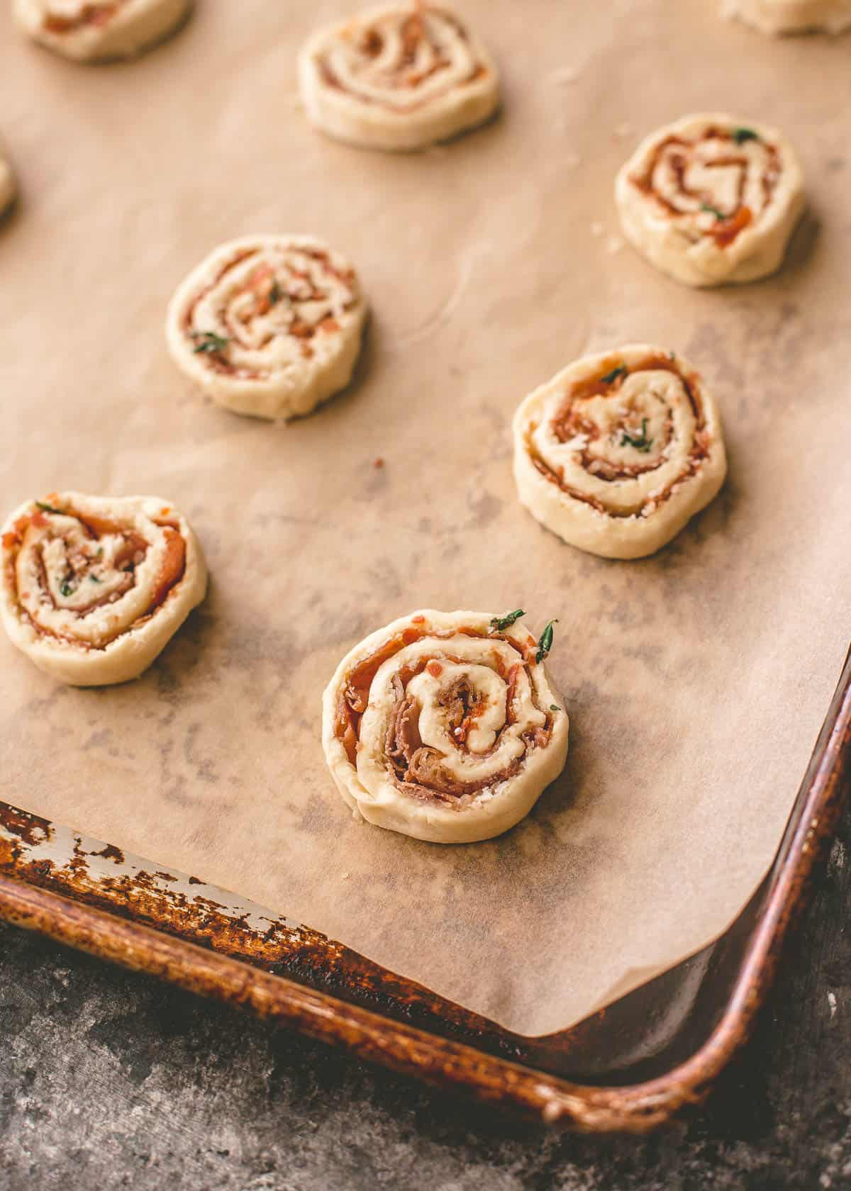 cheese pinwheels on a parchment lined sheet pan