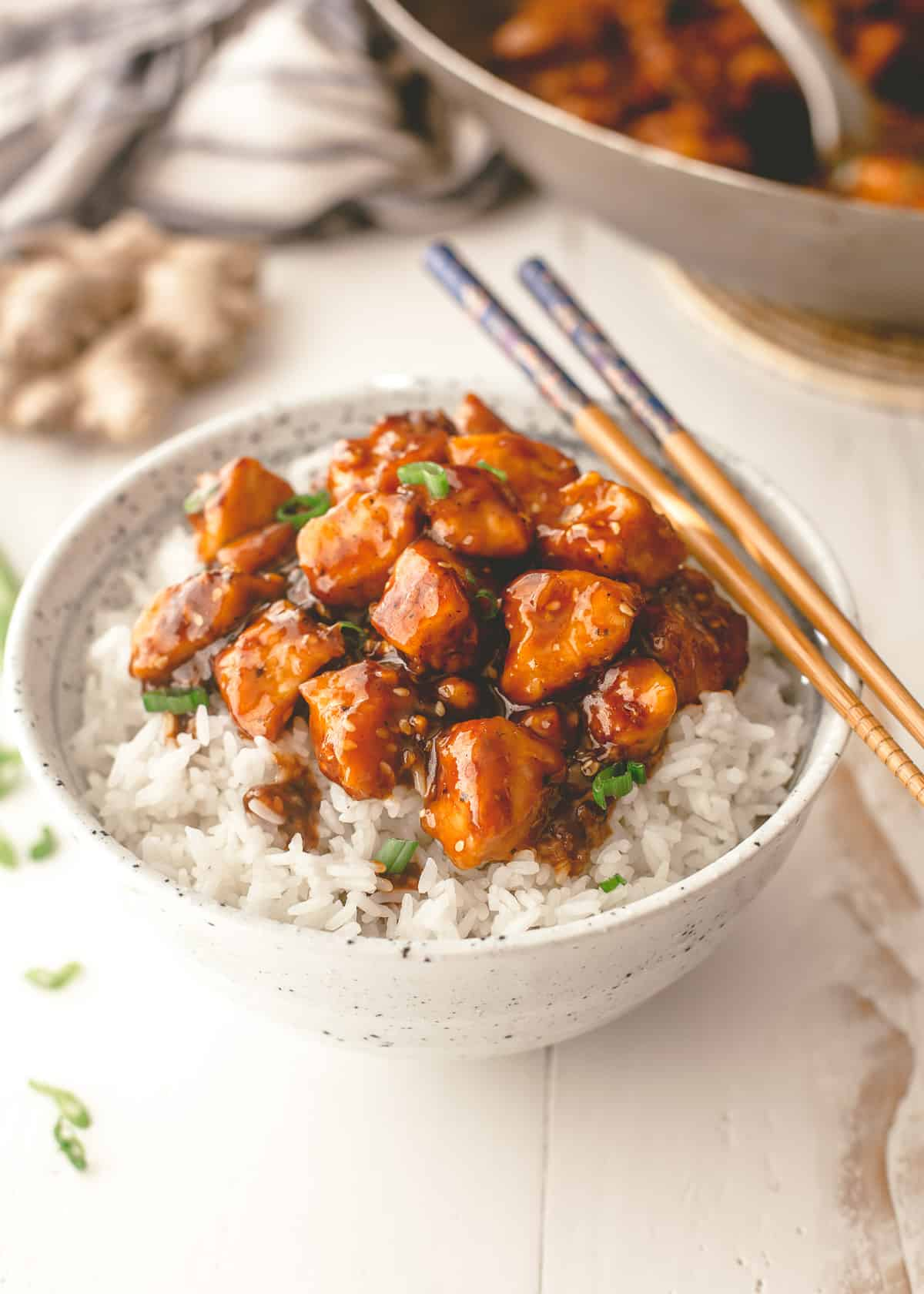 chicken stir fry over rice in a white bowl with chopsticks