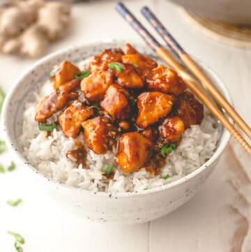 stir fry over rice in a white bowl with chopsticks