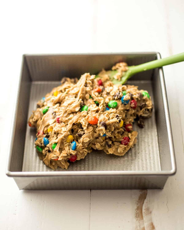 putting cookie dough mix into a baking pan