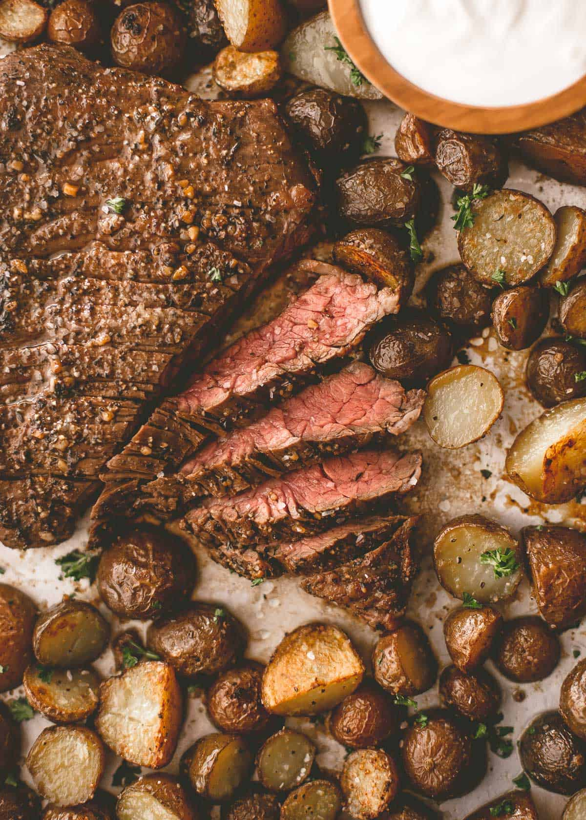 steak and potatoes on a parchment lined sheet pan