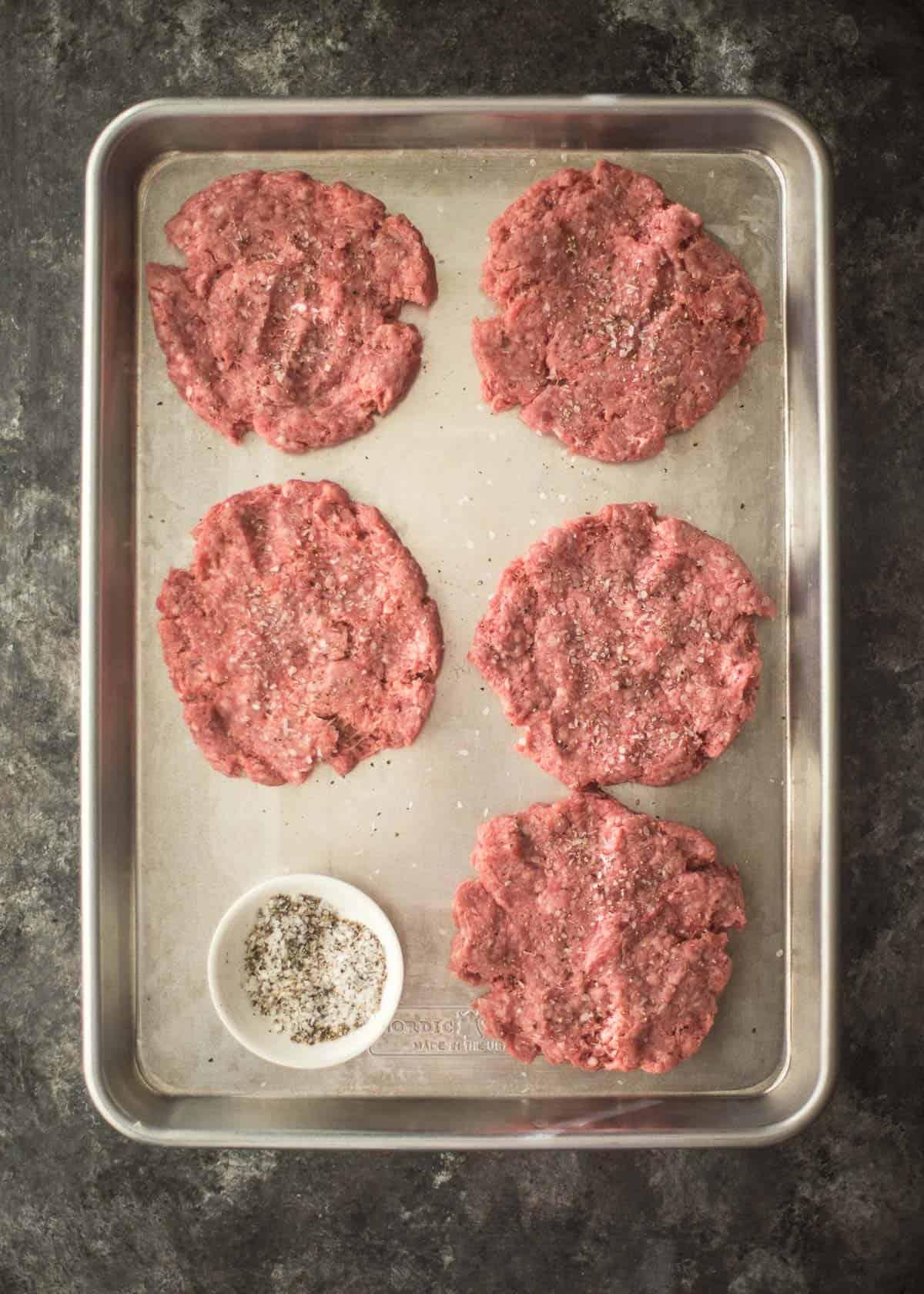 raw hamburger patties on a sheet pan