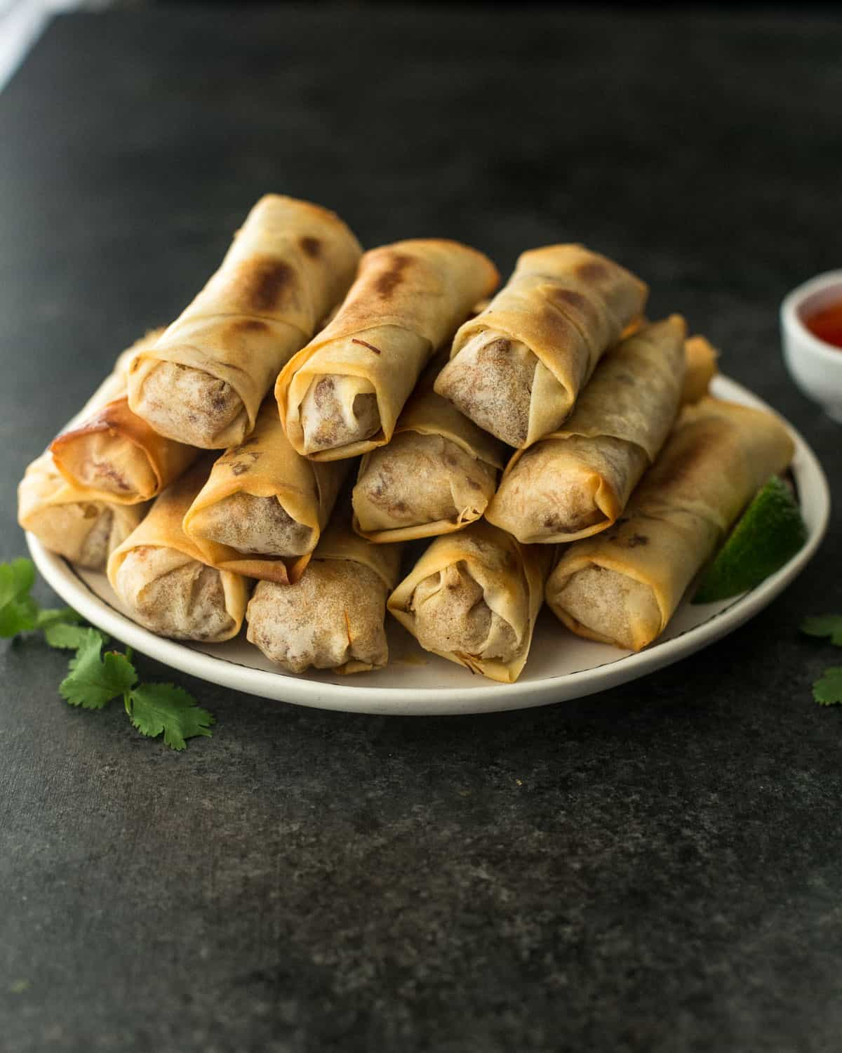 spring rolls stacked on a white plate