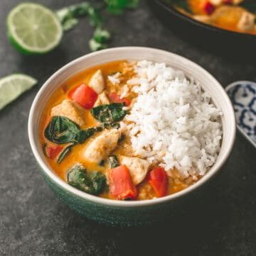 chicken curry over rice in a green and white bowl