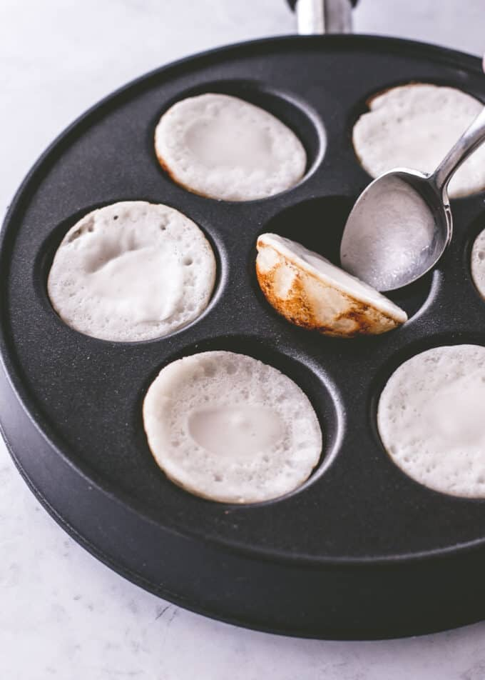 turning coconut pancakes in a pan