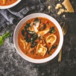 creamy tortellini soup in a white bowl