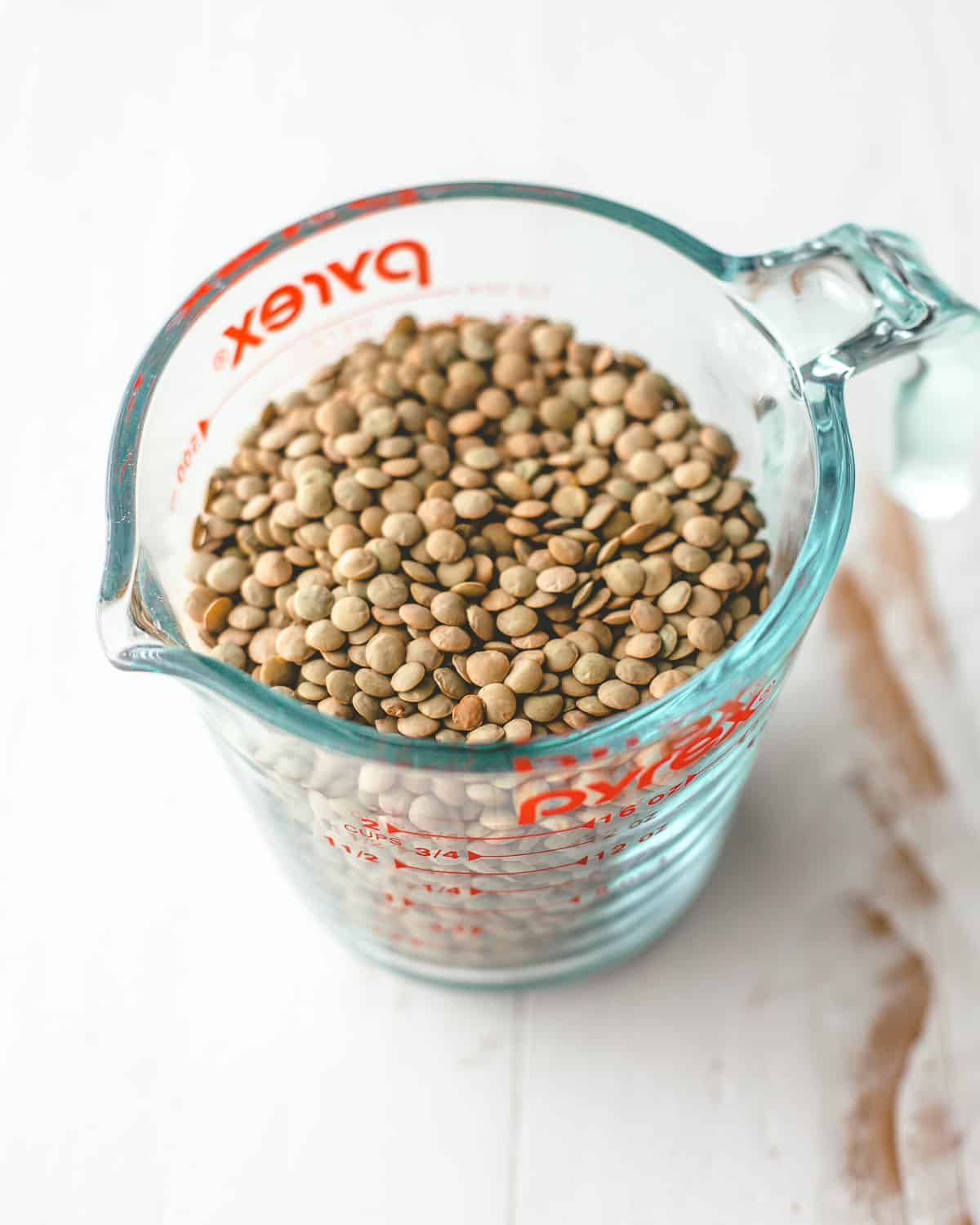 green lentils in a glass measuring cup