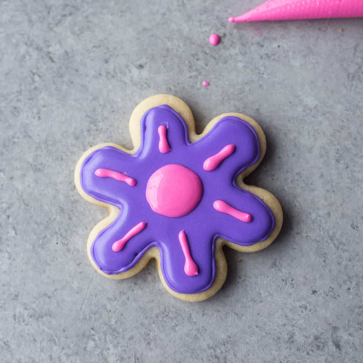 icing a flower shaped sugar cookie