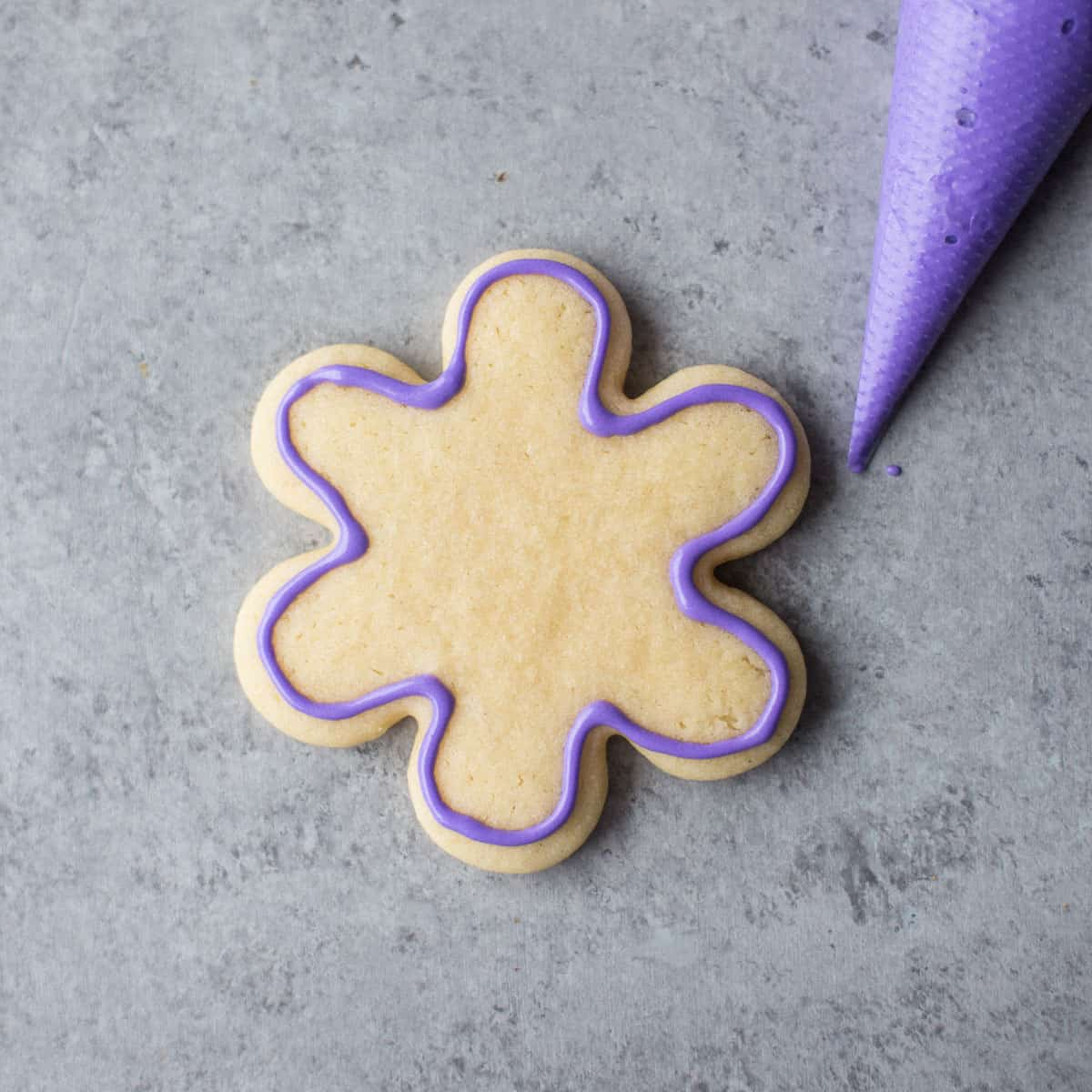 adding purple icing to a sugar cookie