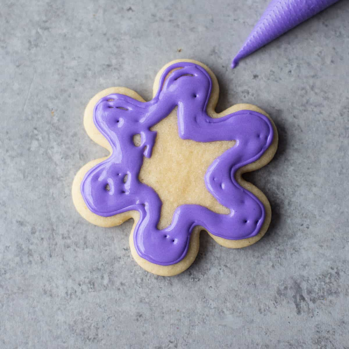 icing a sugar cookie with purple icing