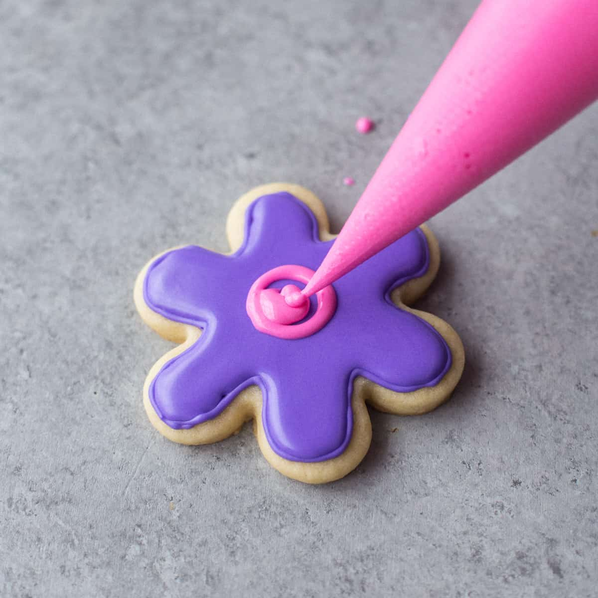 icing a flower-shaped sugar cookie