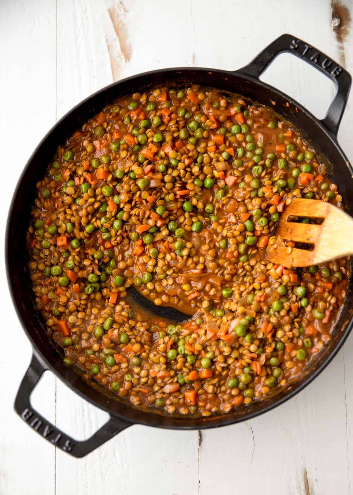 stirring lentils and vegetables in a skillet