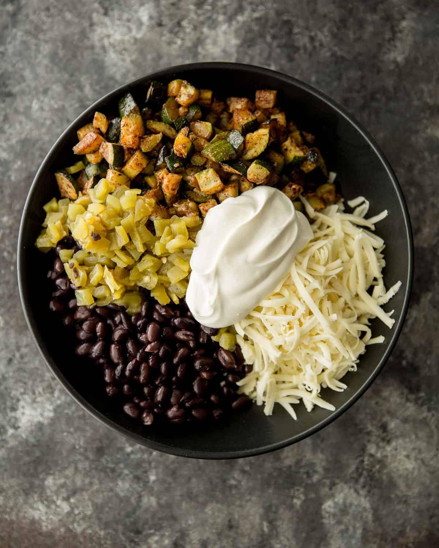 black beans, zucchini, cheese, sour cream in a black bowl