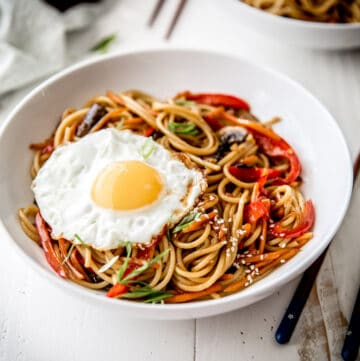 sesame vegetable noodles topped with a fried egg in a white bowl
