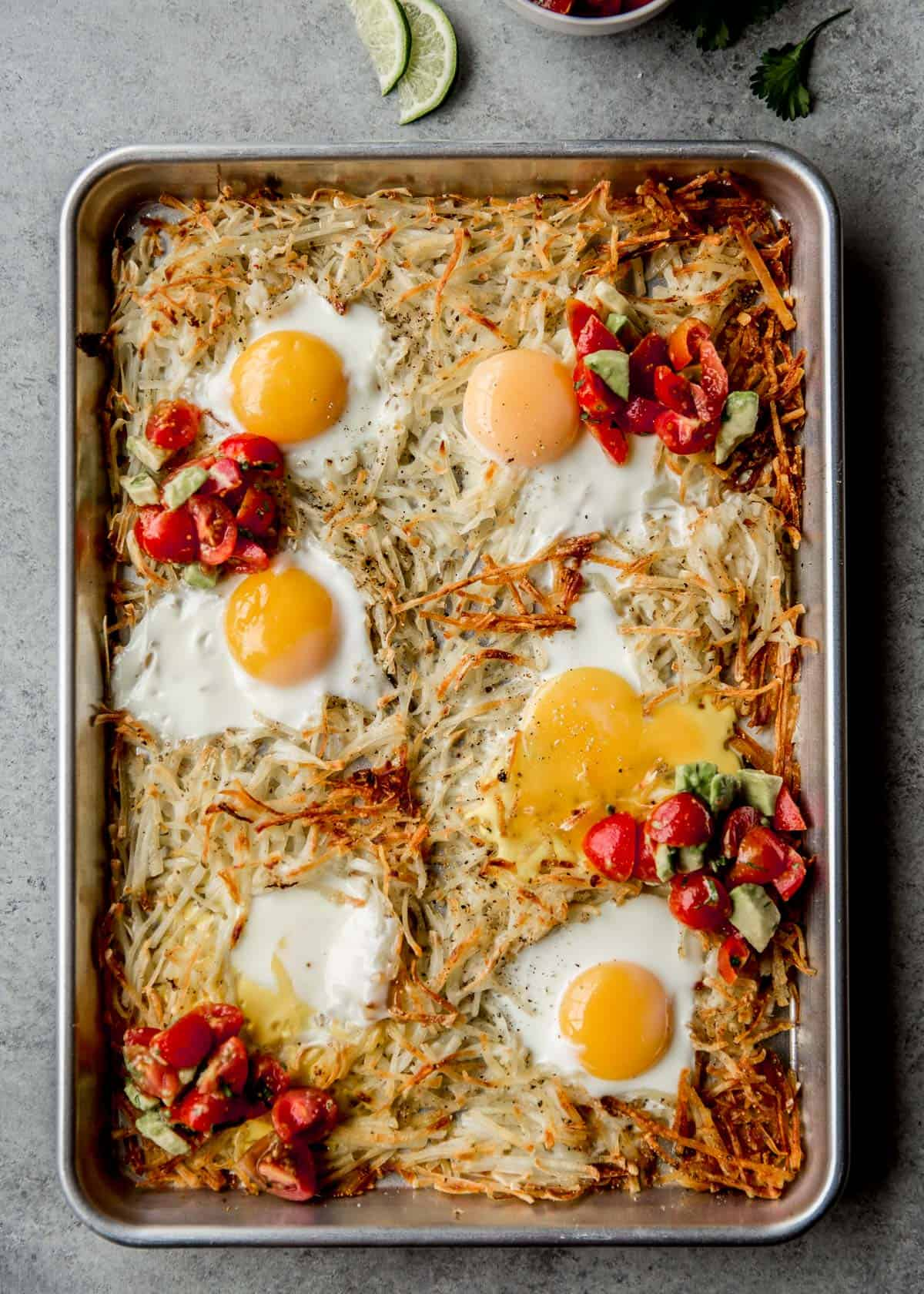 potatoes, eggs, and salsa on a parchment lined sheet pan