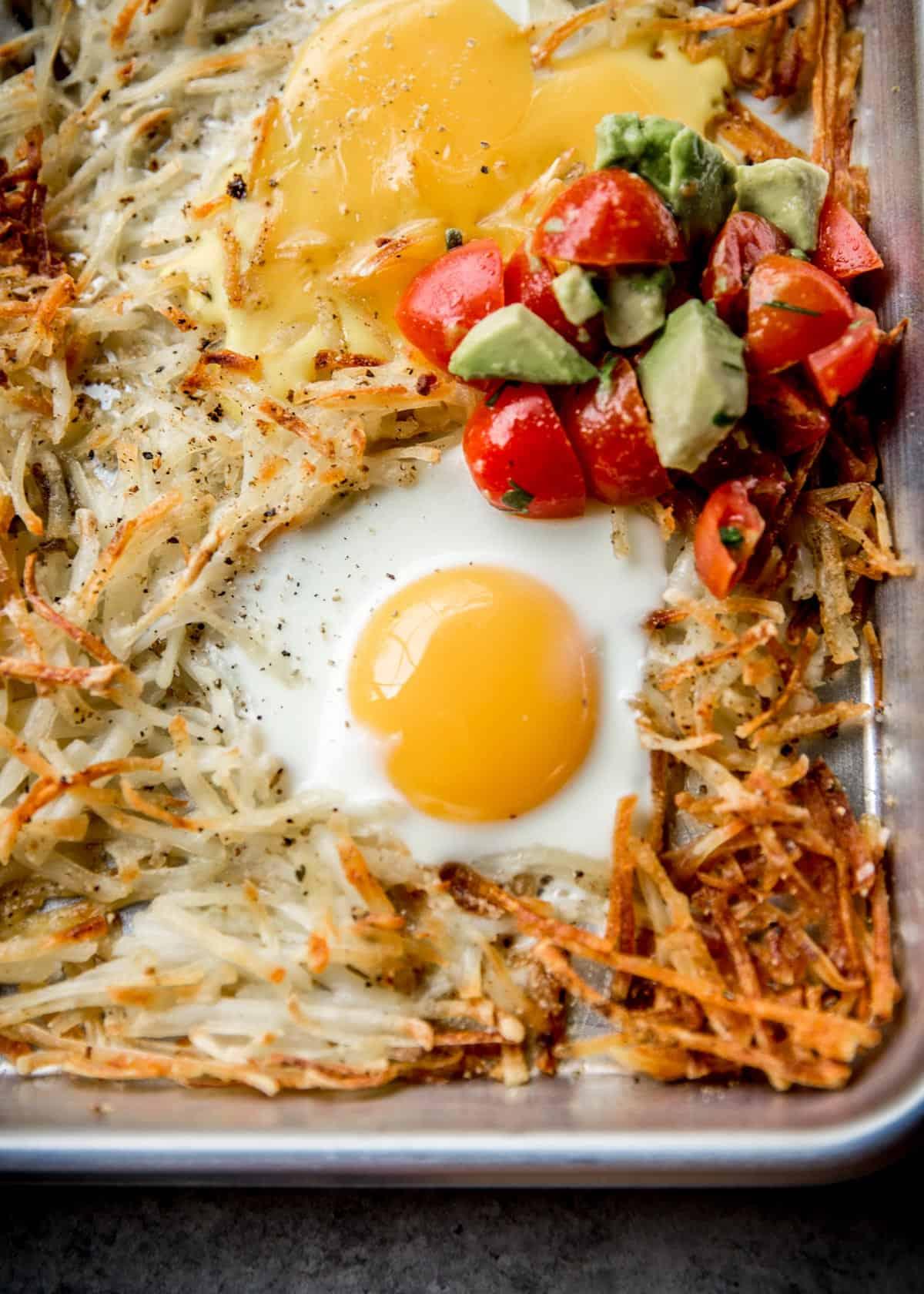 potatoes, eggs and salsa on a sheet pan